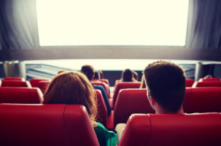 happy couple watching movie in theater or cinema