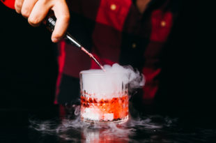 Barman making red smoking cocktail