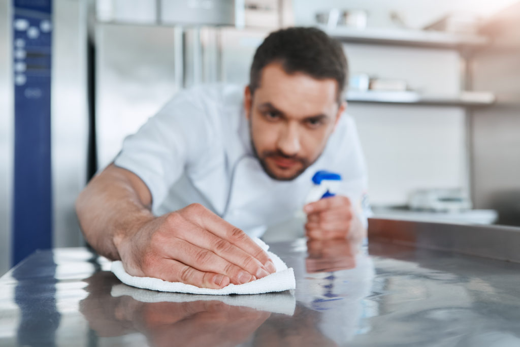 Hygienic precautions. Worker in restaurant kitchen cleaning down after service. Selective focus on his hand