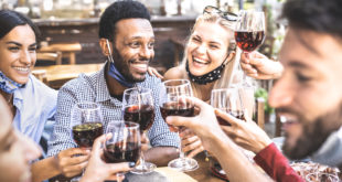 Friends toasting red wine at outdoor restaurant bar with open face mask - New normal lifestyle concept with happy people having fun together on warm filter - Focus on afroamerican guy