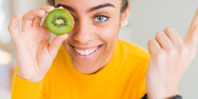 alimentazione salute dieta donna frutta kiwi veg Young african american girl eating green kiwi very happy pointing with hand and finger to the side