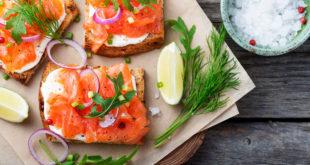 tartina salmone affumicato su tagliere con erbe aromatiche, lime e cipolla e ciotola di sale grosso