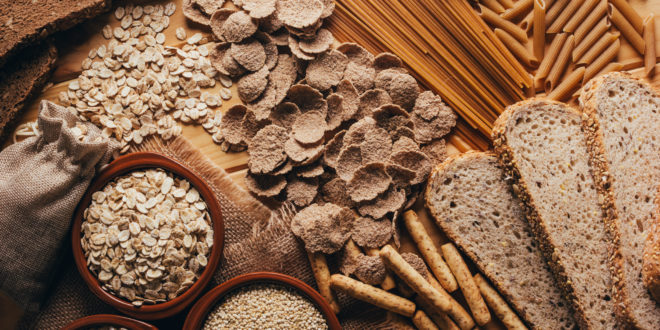 Wooden table full of fiber-rich wholegrain foods, perfect for a balanced diet Tavolo di legno pieno di cibi integrali ricchi di fibre, perfetti per una dieta bilanciata