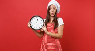 donna con grembiule e cappello da chef regge orologio da muro