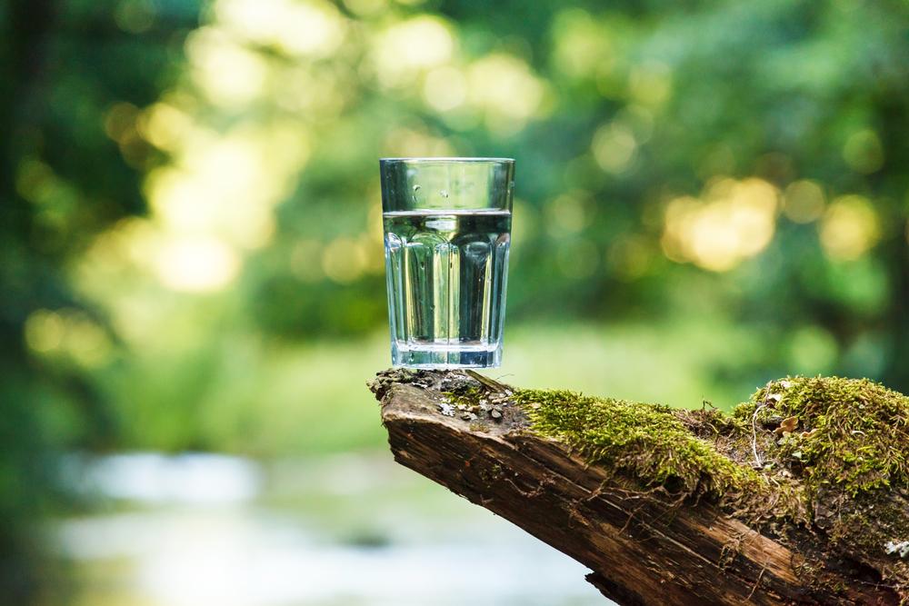 acqua, bicchiere di vetro pieno d'acqau appoggiato su una roccia