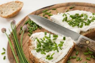 Pane con formaggio spalmabile e erba cipollina su tagliere con coltello