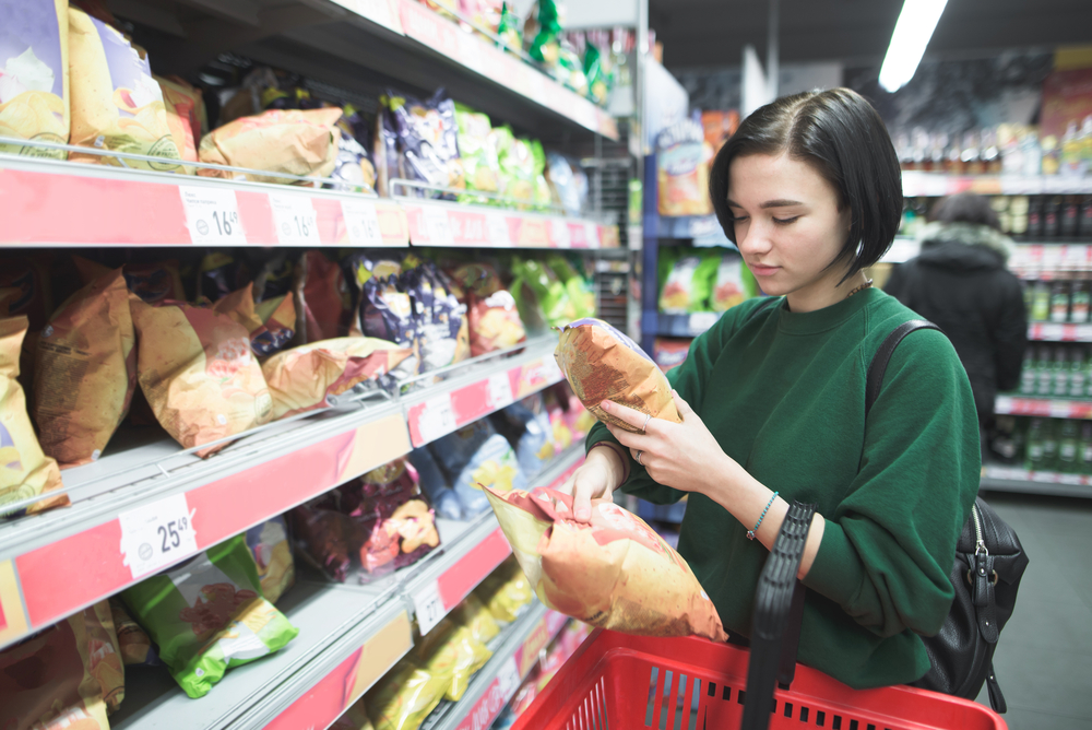 A young girl buys snacks in a supermarket. The girl chooses chips in a supermarket and puts them in a red shopping cart. Shopping in a supermarket.